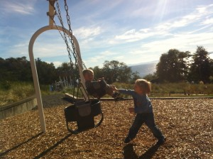 Jayden pushing his baby brother on the swing <3